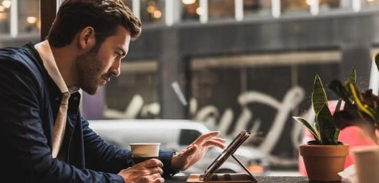 Man met iPad en koffie checkt investeringen in een koffiebar
