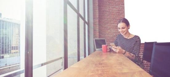 beleggen voor beginners: vrouw zoekt op telefoon meer informatie over aandelen