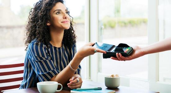 Deze vrouw betaalt contactloos met haar mobiele telefoon