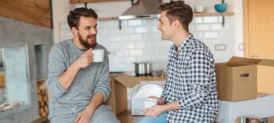 Mannen praten over eigen risico verhogen bij je woonverzekeringen