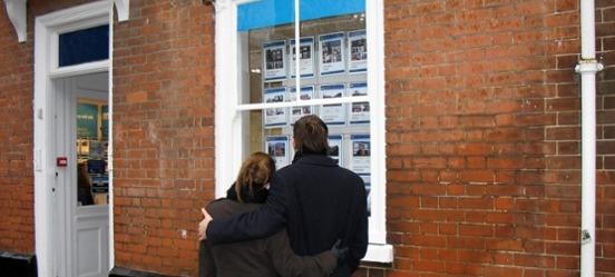 Stel bekijkt huizen met stijgende huizenprijzen